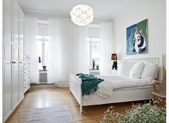Bílou barvu v ložnici rozbíjí barevný vtipný obraz